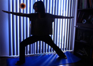 "Photo by Katrina Samuelson ""Taylor Morris, sophmore English major, strikes her ""warrior one"" pose while practicing yoga in her apartment. ""Warrior one"" is one of many standing poses one can use while exercising with yoga."""