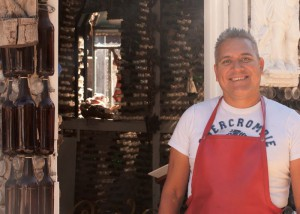 "Photo by Sarah Jane O'Keefe""The owner of Tio's Tacos in downtown Riverside, Martin San-chez, poses in front of his personally crafted chapel located right outside of the restaurant."""