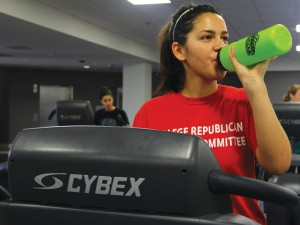 Photo by Fletcher Perkins -- Cassadi Boyd, freshman international studies major, hydrates while working out on the treadmill at the CBU Recreation Center.