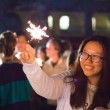 Lauren Koski | Banner Xuan Wang, freshman accounting major, enjoys the festivities of the Lunar New Year Festival as she smiles at the sparkler in her hand.