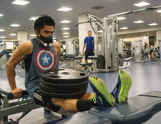 Elbee Castro, junior nursing major, does dips using 180-pound weights in the campus Recreation Center wearing his Training Mask. Katey Lee| The Banner