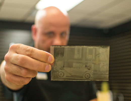 John Flack, general manager of Image One Camera and Video, displays a 160mm negative, different from the usual 35mm size, of a classic car that a patron dropped off to be developed.  Katey Lee | Banner
