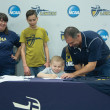 Hannah Tamimi | Banner Davis Galluzzo, 7, signs an Institutional Letter of Intent Oct. 21 with the support of his family to be drafted onto the men's volleyball team with Derek Schmitt, head coach for men's volleyball. Galluzzo was diagnosed with acute lymphoblastic leukemia at 2 years old. He plans to support the men's volleyball team throughout the season.