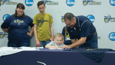 Hannah Tamimi   Banner Davis Galluzzo, 7, signs an Institutional Letter of Intent Oct. 21 with the support of his family to be drafted onto the men's volleyball team with Derek Schmitt, head coach for men's volleyball. Galluzzo was diagnosed with acute lymphoblastic leukemia at 2 years old. He plans to support the men's volleyball team throughout the season.