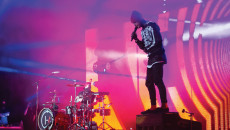 "Tyler Joseph, singer of Twenty One Pilots, performs ""Guns for Hands,"" from the band's previous album ""Vessel,"" on top of his piano. Joshua Dun, drummer, plays drums in the background at the Greek Theater in Los Angeles Oct. 15."