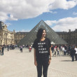 Photo courtesy of Glorify Apparel Sarah Garcia, owner and founder of Glorify, stands in front of the Louvre in Paris, France, and displays one of the brand's ministry-inspired designs.
