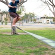 Graham Allgood | Banner Cameron Schaefer, junior electrical engineering major, balances on a slackline tied between two trees near the California Baptist University sand volleyball courts.  Slacklining utilizes body coordination and mental focus for balance.